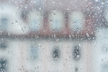 closeup of rain drops on window on blurred building background