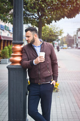 Man in a jacket and suit on a European street with coffee in his hands. Business guy fashion clothes. Autumn landscape, portrait. stock photo