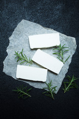Sliced feta cheese with rosemary on rustic paper.