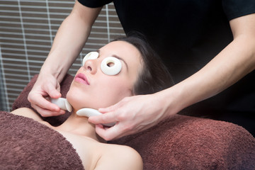 Young woman in spa having face massage