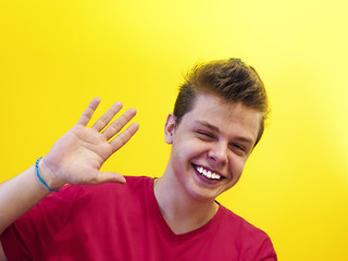 Attractive smiling young guy waving his hand