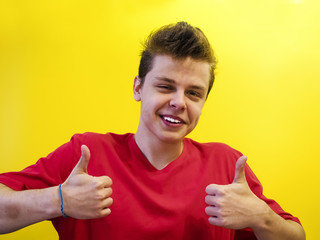 super satisfied young casual man making ok thumbs up sign hands on yellow background