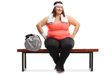Overweight woman with a towel sitting on a bench next to a sports bag