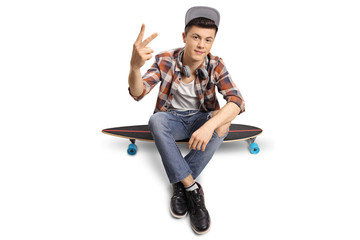 Teenage hipster sitting on a longboard and making a peace sign