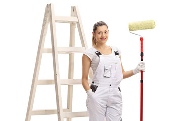 Female painter holding a paint roller in front of a ladder
