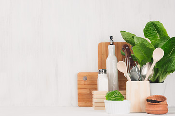 Natural beige and brown wooden kitchenware and green plant on light white wood background, copy space.