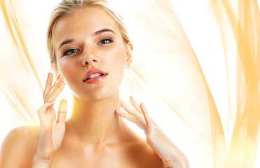 Young girl touching her perfect skin on wavy orange background. Skin care concept