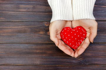 red heart in hands closeup on wooden background