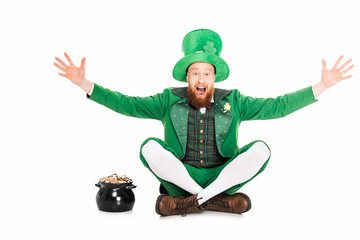 excited leprechaun gesturing and sitting at pot of gold, isolated on white