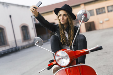 Portrait of fashionable young woman sitting on red motor scooter taking selfie with cell phone