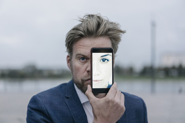 Businessman holding cell phone with image of a woman in front of his eyes