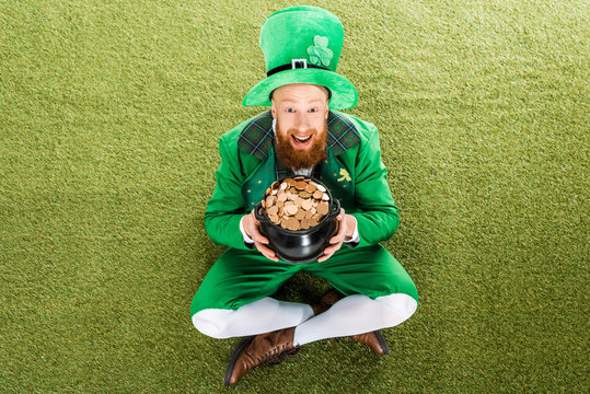 excited leprechaun with pot of gold sitting on green grass