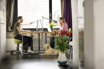 Man and woman with dog working at desk at home