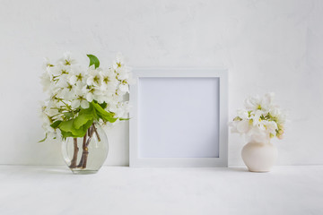 Mockup with a white frame and white flowers