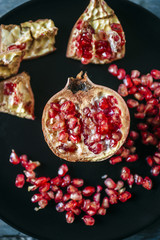 Half of pomegranate and pomegranate seed on black plate, close-up