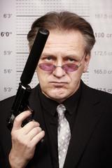 Older rent killer man portraited with silenced pistol in front of mug board
