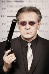 Rent killer man portraited with silenced pistol in front of mug board