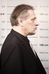 Criminal man portraited in front of mug board