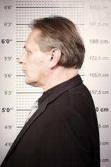 Criminal man portraited in front of mug board