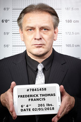 Criminal man portraited in police station style in front of mug board with data tablet