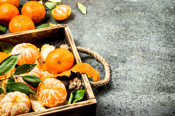 Fresh tangerines on a wooden tray.