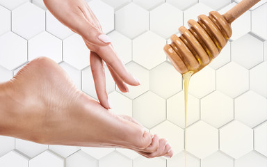 Honey flows down from spoon near female foot.