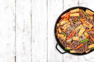 Delicious soba with tofu skin and vegetables in a cast iron pan on light wooden background, top view