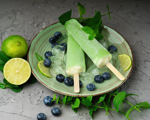 Homemade kiwi, lime, mint ice cream or popsicles with ripe blueberries on green plate and gray concrete table. Frozen fruit juice, vintage style, close up.