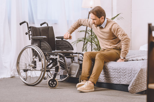 man with disability trying to sit on wheelchair from bed