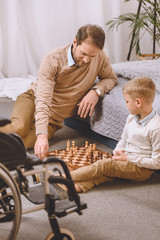 father with disability and kid playing chess on floor
