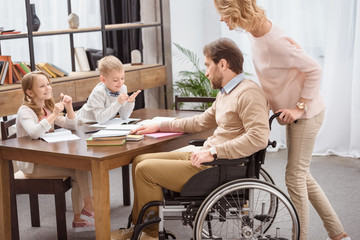 father on wheelchair and mother teaching kids at home