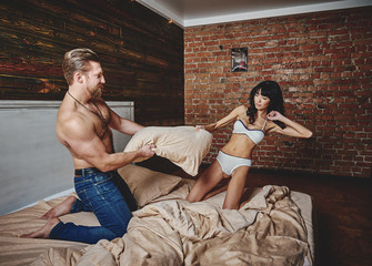 Strong Man and beautiful woman lying on the bed intimate atmosphere. Luxurious furniture and beautiful interior. A girl with black hair is a man without a shirt. Love and tenderness.