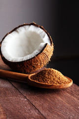 scoop of brown sugar with coconut on wooden background