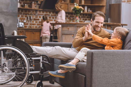 happy little son with smiling disabled father giving high five and wheelchair standing near sofa