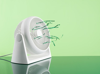 Plastic white electric fan in working mode with Text Space on green background