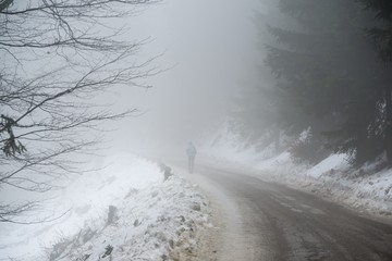 Man hiking within the trees on the hill in winter. Slovakia