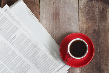 White coffee cup and news paper on wood table