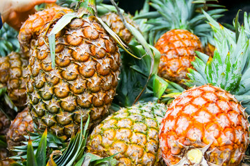 pineapples on fruit stand in fresh market