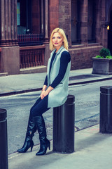 Woman Street Fashion in New York. Dressing in long vest, black fitted T shirt, pants, long boots, Eastern European businesswoman sitting on metal pillar on vintage street, relaxing. Filtered effect..