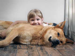 A small child lies on a huge dog