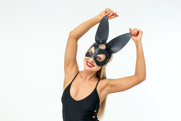 Smiling sexy blonde woman wearing bunny mask and bodysuit posing and looking at camera.  Background is not isolated.