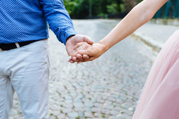 close up photo of young couple holding hands on street in summer