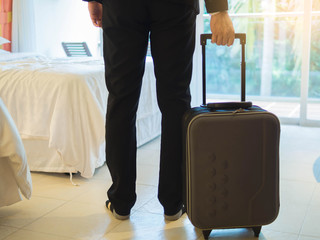 Businessman with his suitcase at the hotel room