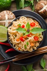 Instant noodles in black bowl on wooden background.