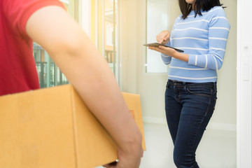 Woman receiving package and signing on digital tablet from delivery man.