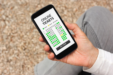 Hand holding smart phone with online tickets concept on screen. All screen content is designed by me