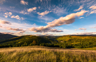 grassy slope in mountainous countryside at sunset. beautiful landscape with gorgeous cloudscape over the hills of Carpathian mountains. location Nyzhni Vorota, Volovets district of TransCarpathia, UA