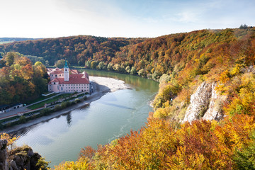 Weltenburg monastery and Donaudurchbruch at the Danube river in Bavaria, Germany surrounded by orange autumn colored trees