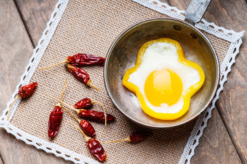 Bell pepper egg ring on a cooking pan and dried chili peppers