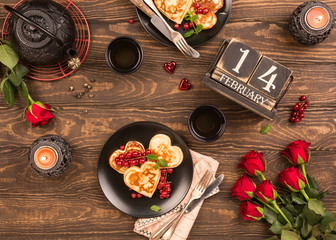 Valentine's day flat lay with delicious pancakes in form of heart, green tea, black teapot, candles and roses. Valentines day concept greeting card. Top view.